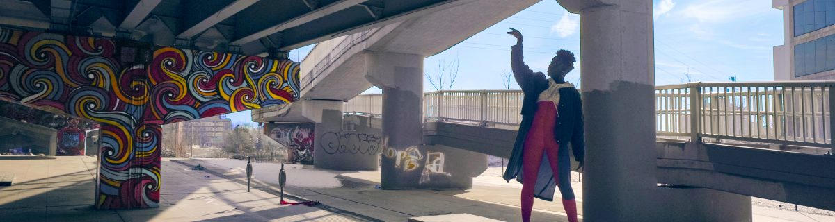 A woman dances beneath a highway underpass