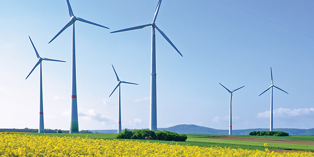 A landscape photo of wind turbines against a blue sky