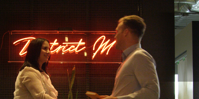 A man and a woman speaking in front of a neon sign