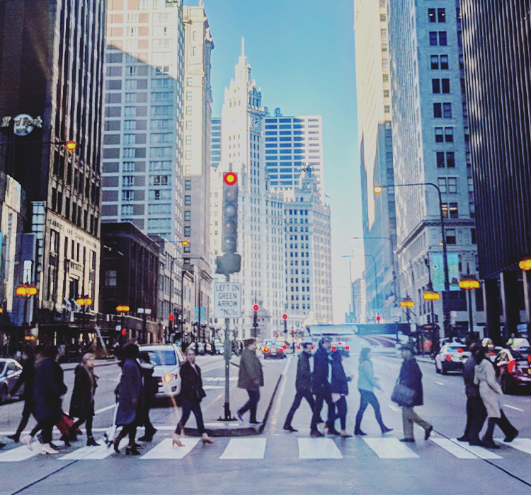 People cross a busy downtown intersection in Chicago