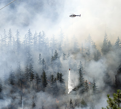 A helicopter dispenses water from the air to combat wildfires
