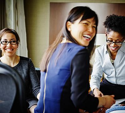 Three women of colour smiling