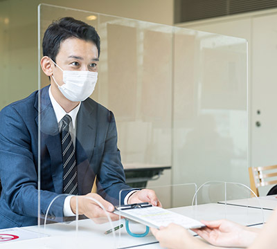 Two people with masks talking across an acrylic partition