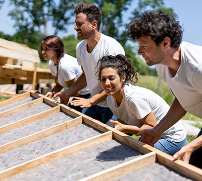 Four people helping lift the framing for a house
